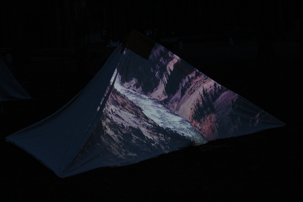 image showing a tent in Yellowstone National Park with projection of Artist's Point on the side